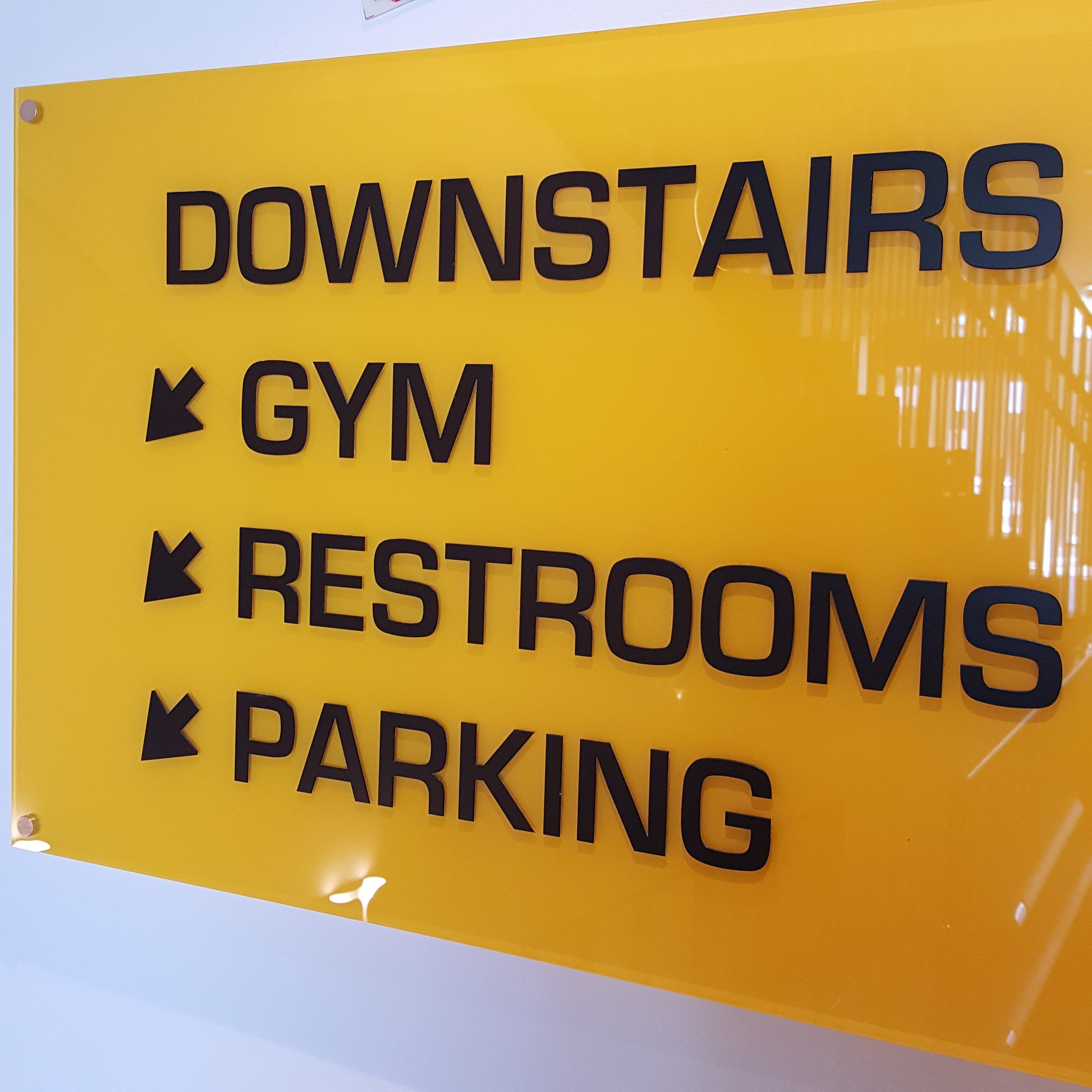 """Sign in a hotel gym designed by fit for business, sign reading """"Downstairs; gym, restrooms, parking"""""""